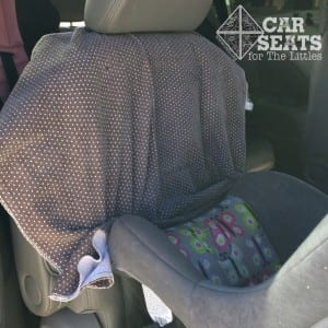 Old blankets are great for safely protecting the back seat from little feet